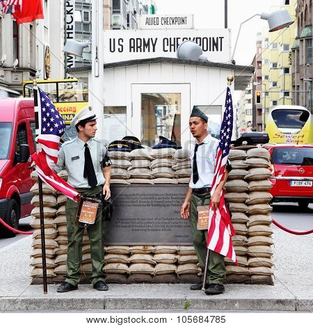 BERLIN, GERMANY - August 22, 2012: Unidentified young men dressed as American soldiers stand near the checkpoint Charlie.The most famous crossing point between East and West Berlin after WW2.