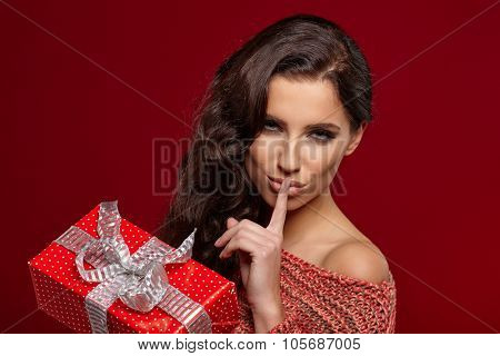 Girl with  x-mass present isolated on red background