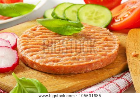 detail of raw burger patty and vegetables on wooden cutting board