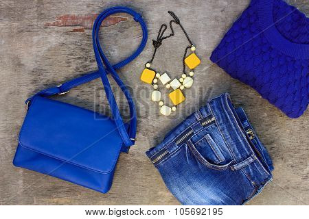 Women's clothing and accessories: blue sweater, jeans, handbag, beads on wooden background.