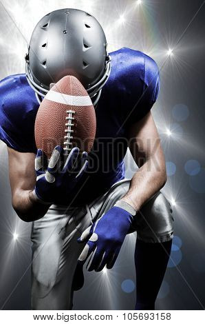 Upset American football player kneeling while holding ball against spotlights