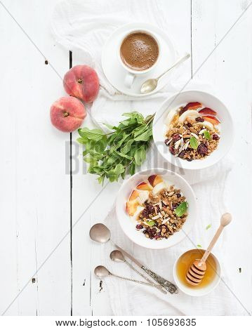 Healthy breakfast. Bowl of oat granola with yogurt, fresh fruit, mint and honey. Coffee, vintage sil