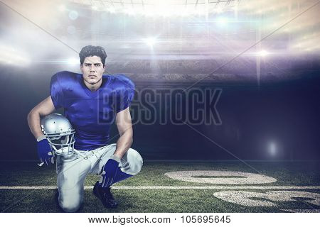 Portrait of confident American football player holding helmet against american football arena