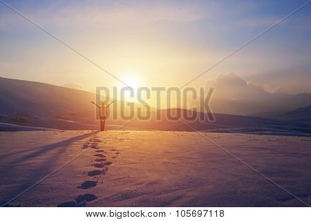 Happy joyful woman having fun outdoors in winter, standing on the mountains with raised up hands on the mountain covered with snow, enjoying beautiful sunset