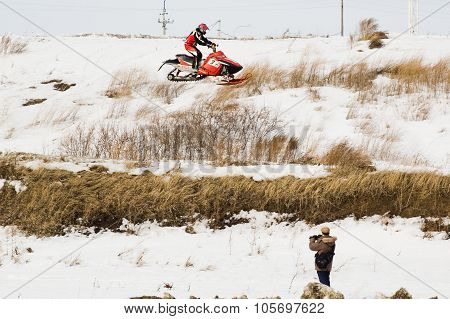 Flying of sportsman on snowmobile and press man