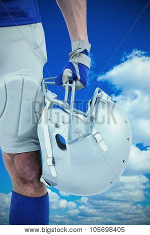 Close-up of American football player holding helmet against low angle view of blue sky