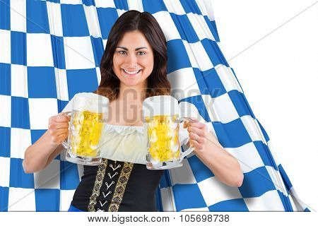 Pretty oktoberfest girl holding beer tankards against blue and white flag