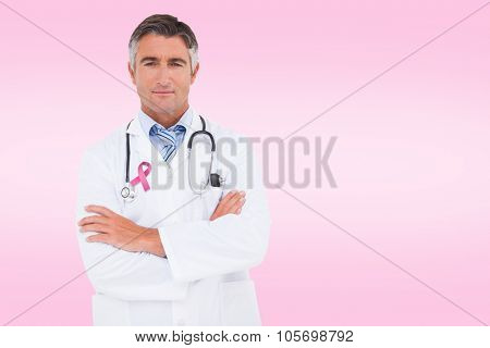 Serious doctor looking at camera against pink
