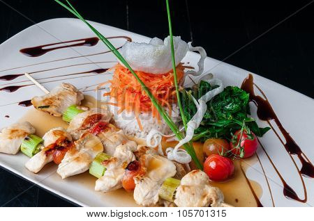 Two skewers of chicken and leeks, served with vegetables
