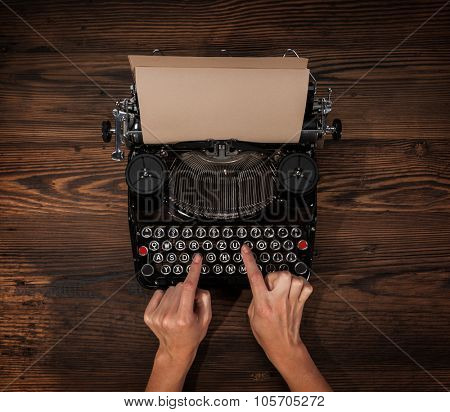 Woman typing on an old typewriter, placed on wooden table