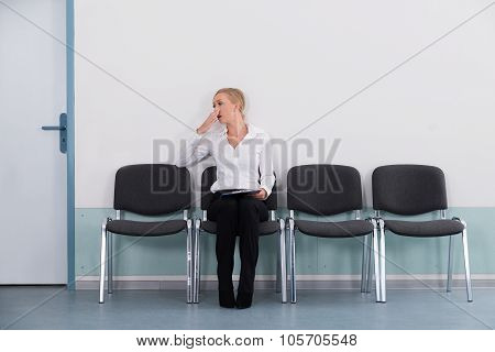 Businesswoman Yawning While Sitting On Chair