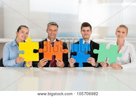 Businesspeople Holding Multi-colored Puzzles