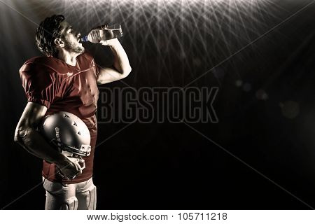 Thirsty American football player in red jersey drinking water against spotlights