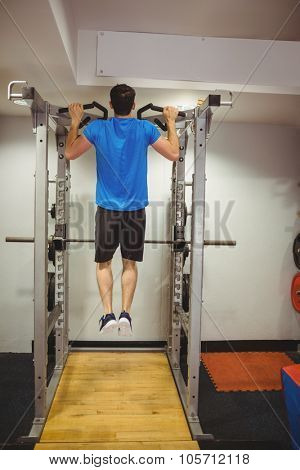 Fit man doing pull ups at the gym