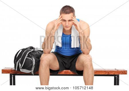 Sad young athlete sitting on a wooden bench and looking down isolated on white background