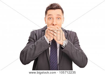 Studio shot of a shocked young businessman covering his mouth and looking at the camera isolated on white background