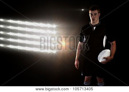 Rugby player holding a rugby ball against spotlights