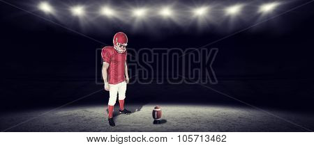 Unsmiling american football player looking down against rugby stadium