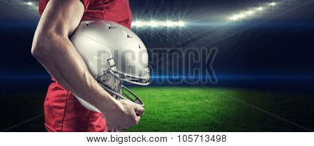 American football player with helmet against rugby stadium