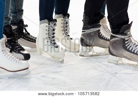 people, winter sport and leisure concept - close up of legs in skates on skating rink