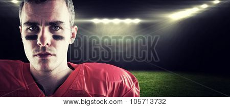 Portrait of a serious american football player looking at camera against rugby stadium