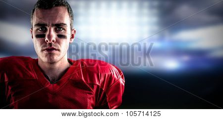 Portrait of a serious american football player looking at camera against sports pitch