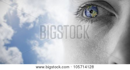 Close up of eye looking up against bright blue sky with clouds