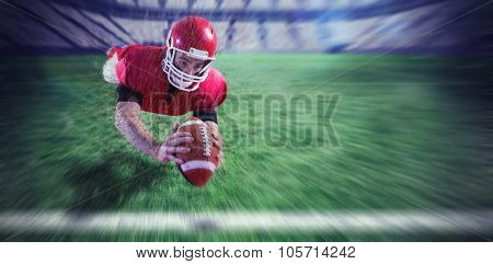 American football player catching football against rugby pitch