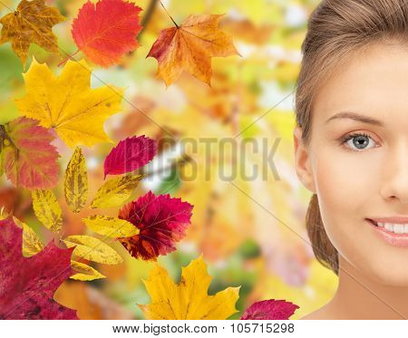 beauty, people and season concept - beautiful young woman half face over autumn leaves background