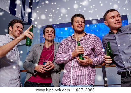 winter, nightlife, friendship, leisure and people concept - group of smiling male friends with beer bottles drinking at bachelor party nightclub and snow effect