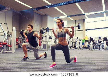 sport, bodybuilding, lifestyle and people concept - young man and woman with barbell flexing muscles and making shoulder press lunge in gym