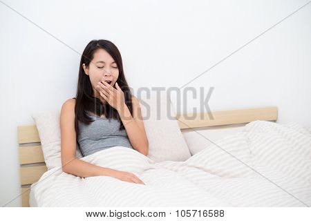 Woman just wake up and sitting on bed