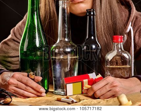 Girl  drinking alcohol and smokes cigarettes in solitude. Bottles and cigarettes in the foreground