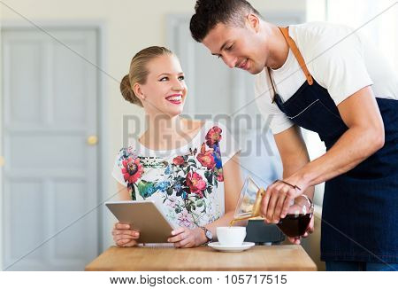 Waiter serving customer at the coffee shop