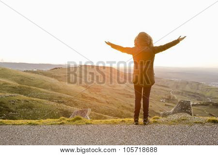 Woman in the montains with open arms at the sunset