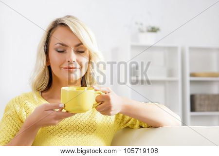 Beautiful woman enjoying the smell of coffee in the morning.