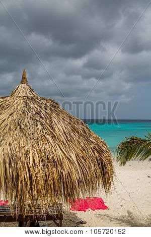 Pink Towels Under Thatched Hut And Stormy Skies