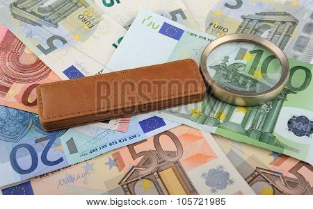 Magnifying glass lying on Euro banknotes
