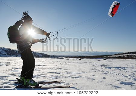 Snowkiting (kiteboarding) - Sportsman Glides On Skis At Sunset