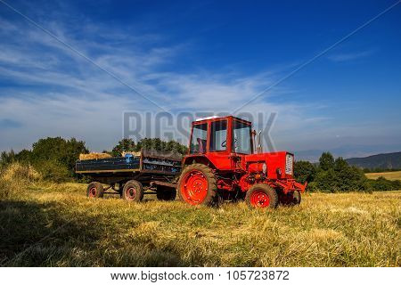Old Red Tractor On The Agricultural Field
