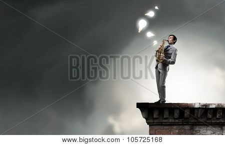 Young man on building roof playing saxophone
