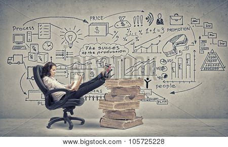 Young businesswoman sitting in chair with her legs on pile of books