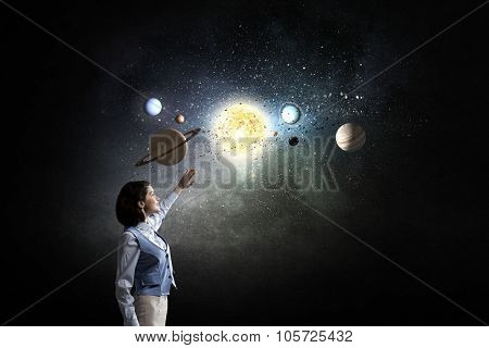 Young businesswoman blinded with light of planets