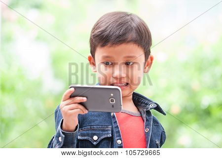 Little boy takes selfie with mobile phone