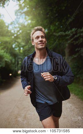 Healthy Young Man Jogging Through A Park