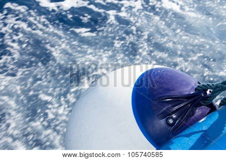 Seascape with water trail from boat with focus on white ball fender