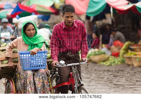 MANDALAY,MYANMAR,JANUARY 17, 2015 : A couple of vegetable seller is riding a sidecar bicycle in the muddy street of the Zegyo outdoors market, in Mandalay, Myanmar (Burma).