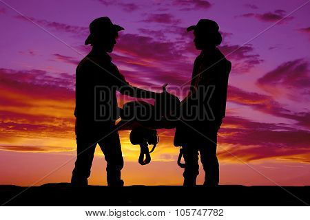 Silhouette Of Two Cowboys Holding A Saddle In The Sunset