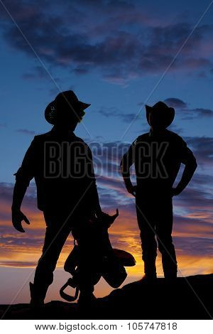 Silhouette Of Two Cowboys In The Sunset One Hold Saddle