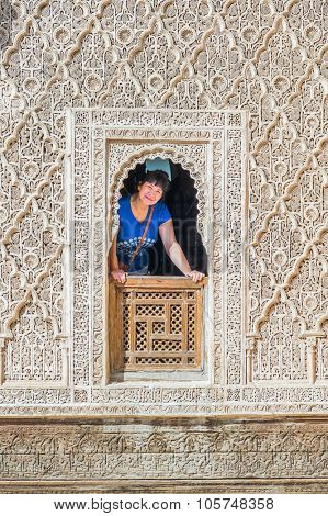 MARRAKESH, MOROCCO, APRIL 16, 2015: Young woman in window of The Ben Youssef Madrasa